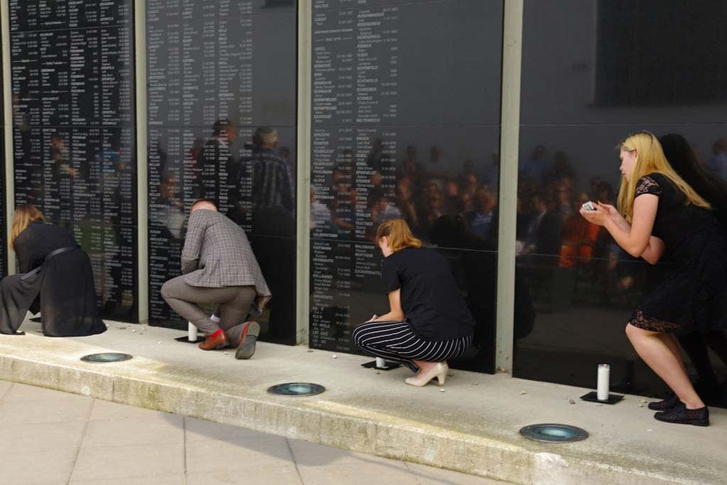 Local students from Leonard Stockel High School light memorial candles in front of the name tablets