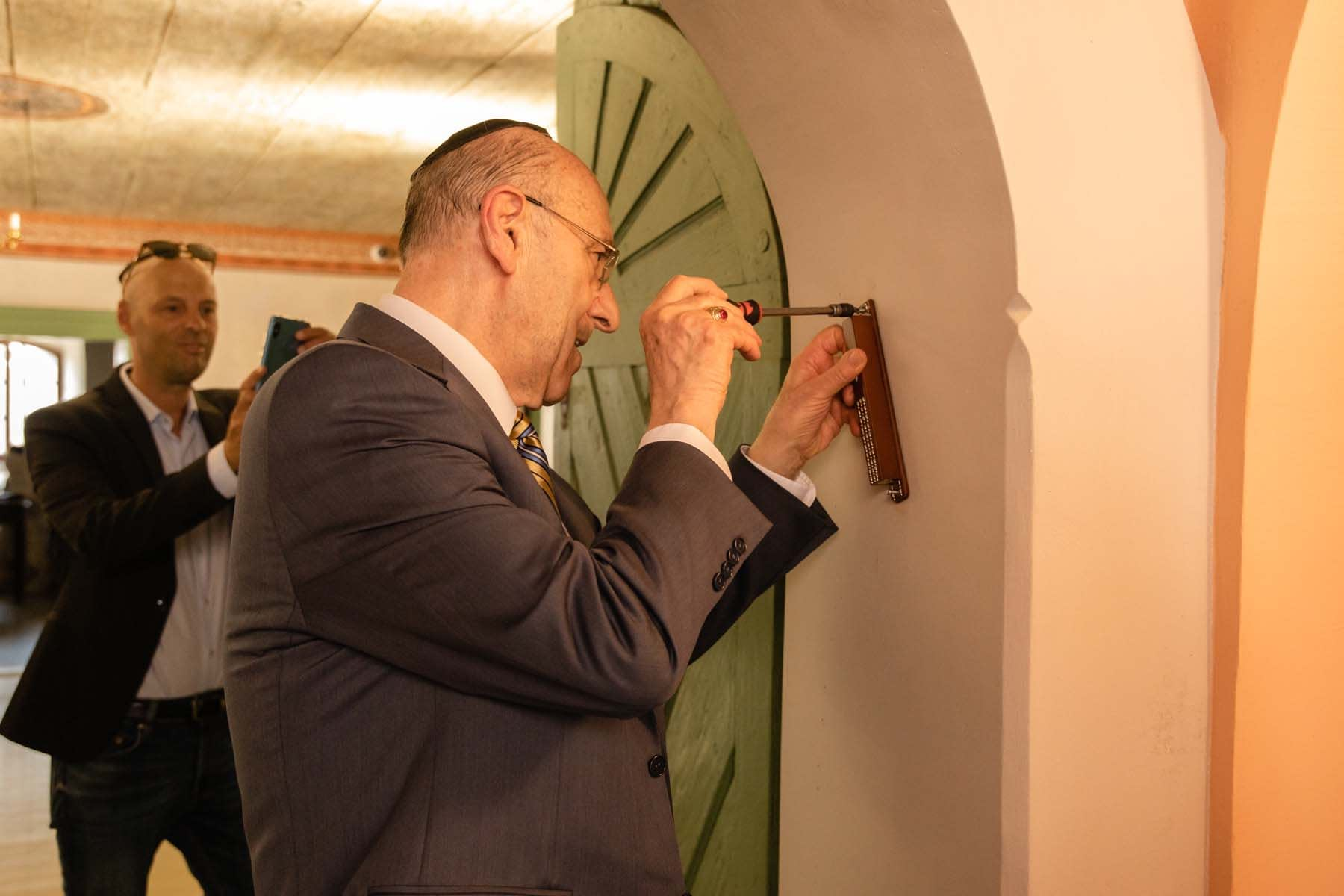 Mr. Emil Fish, together with Mr. Paul Packer and representatives of Jewish religious communities in Slovakia, attached a mezuzah to the doorpost of the entrance door