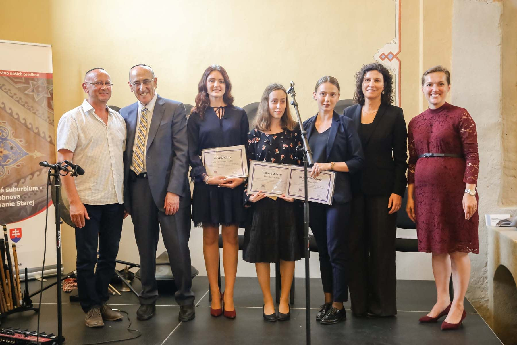 The three winners of the essay contest pose on stage with Mr. Josef Jarina , Mr. Emil Fish, Ms. Orit Stieglitz, and Ms. Anna Humbert