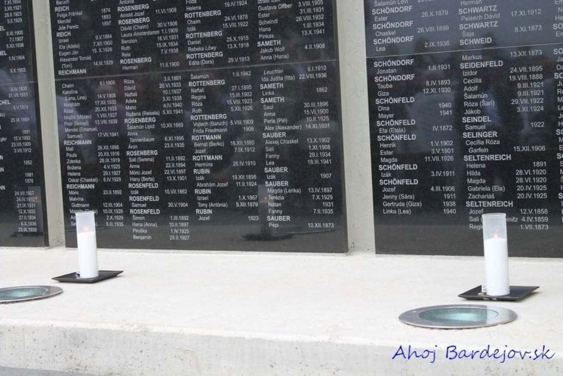 Lit candles in front of the Name Tablets